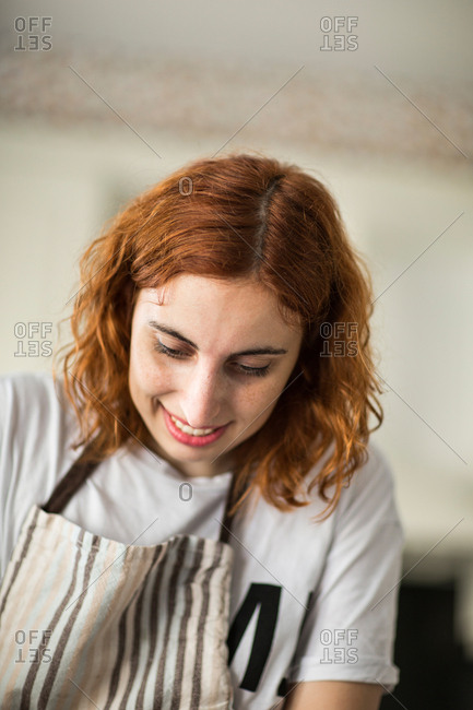 Woman putting cream on tarts