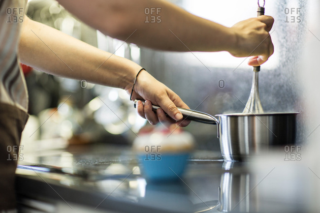 Hands of cook mixing and heating ingredients on a stove Horizontal indoors shot