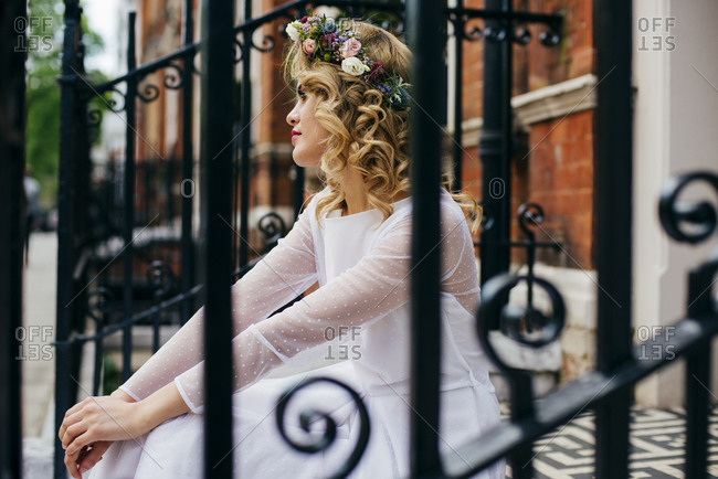 Side view of woman in white gown and flower-made headdress. Horizontal outdoors shot.