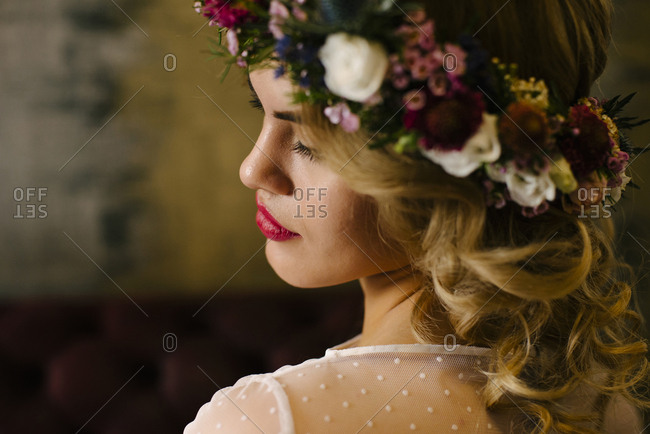 Young gorgeous woman wearing flower-made chaplet posing with eyes closed.