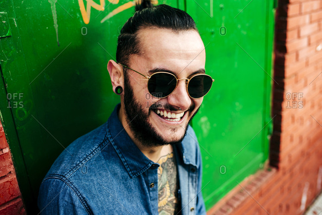 Portrait of laughing hipster man in sunglasses leaning on colorful wall on street.
