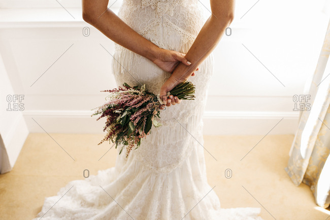 Crop back view of elegant woman in gorgeous wedding dress posing with flowers in hands.