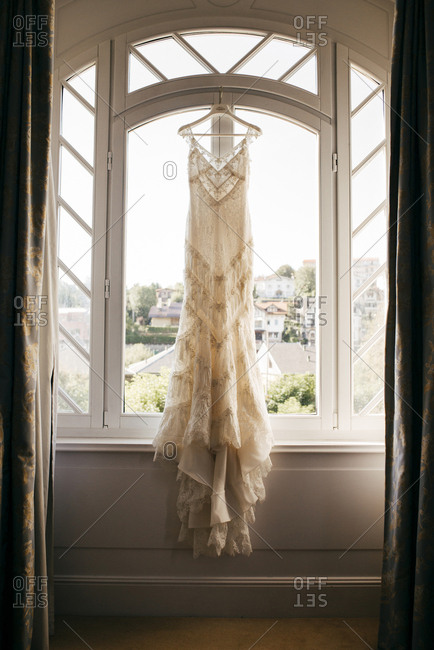 Gorgeous wedding dress on hanger in window.