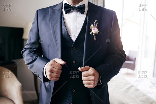 Faceless shot of man wearing wedding elegant suit and posing in room.