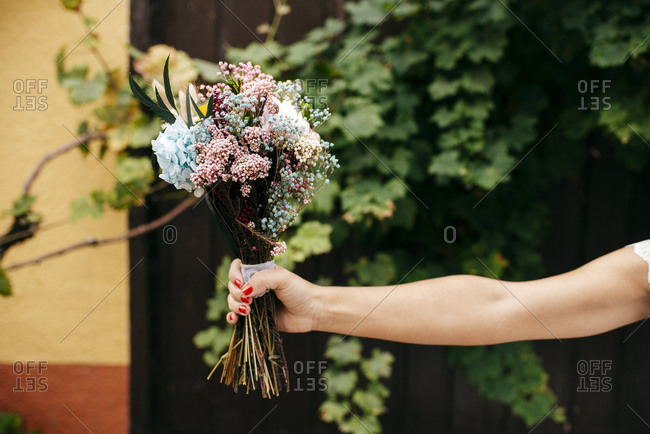 Hand of unrecognizable person holding flowers bouquet. Horizontal outdoors shot.