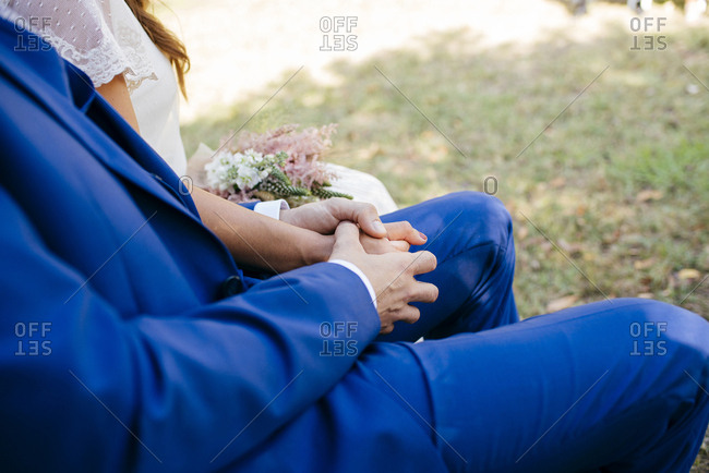 Crop groom and bride holding hands while sitting on bench.