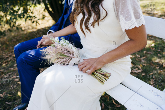 Faceless shot of newlyweds sitting on bench and holding hands.