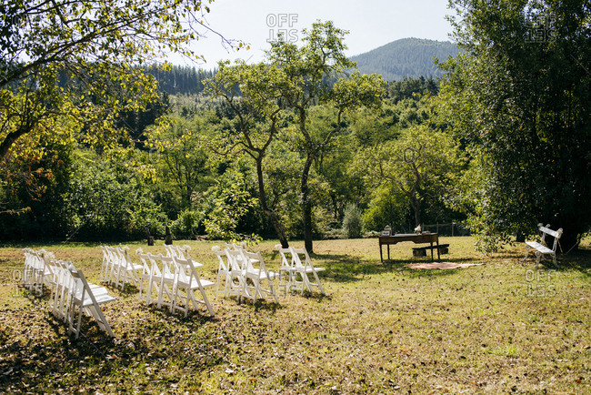 Rows of chairs and table on meadow for marriage registration.