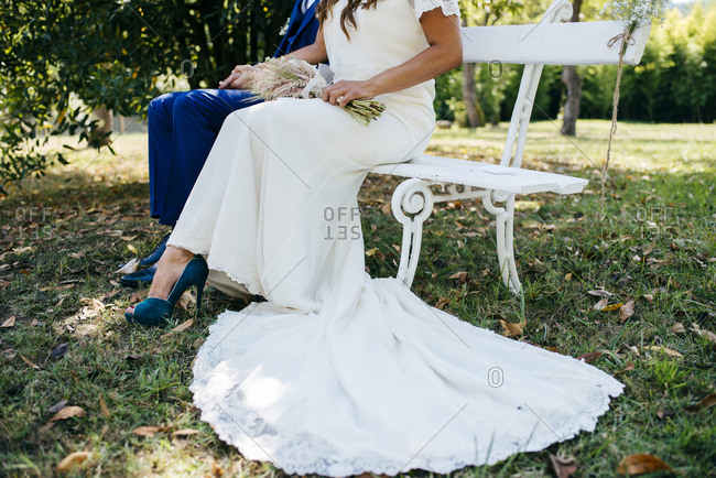 Crop bride and groom on bench