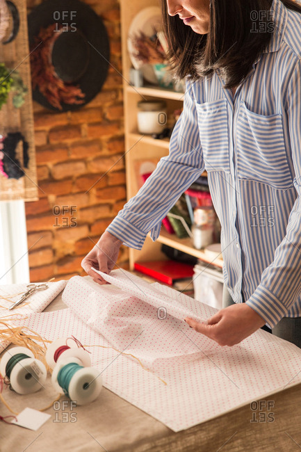 Crop woman in shirt working in craft shop wrapping box with paper.