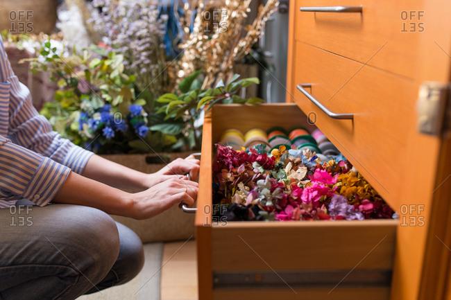 Woman in craft shop choosing flowers