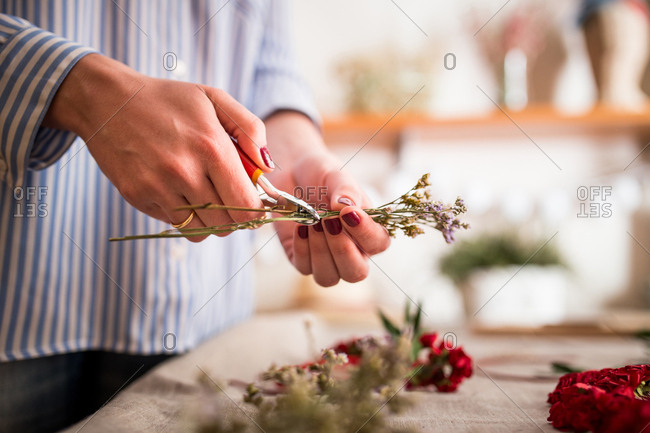 Faceless woman cropping small flowers for creating headdress in craft shop.