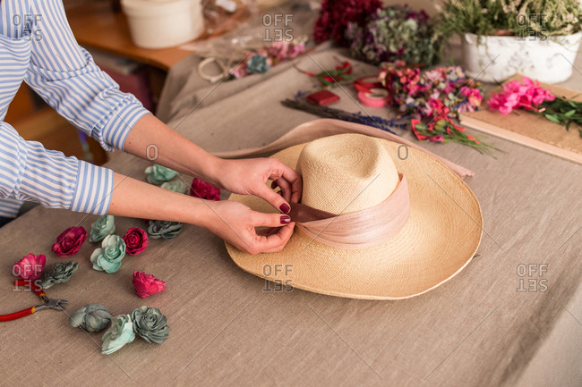 Crop person decorating hat with flowers