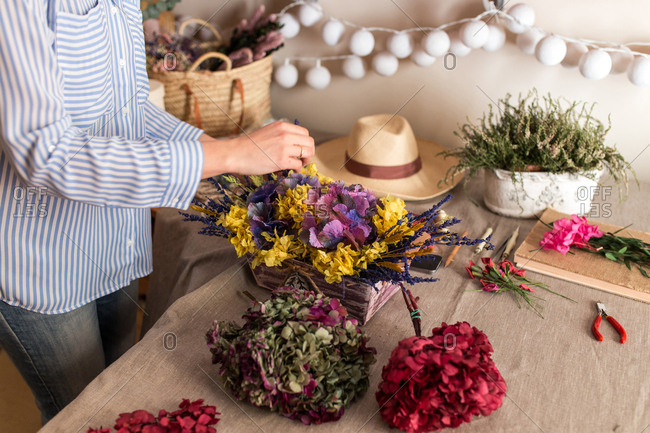 Crop woman arranging flowers