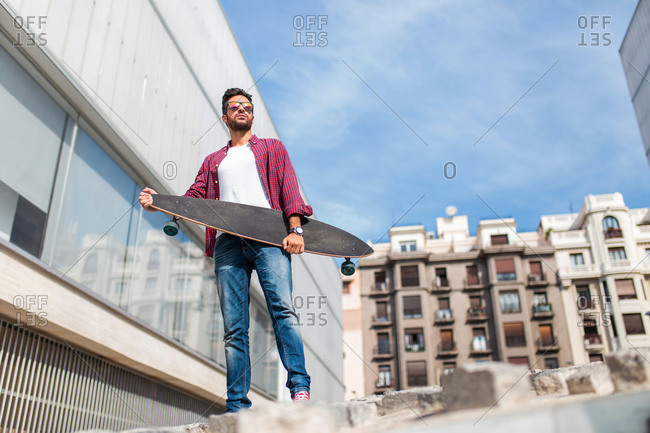 Young bearded man posing on urban background with skateboard in hands.