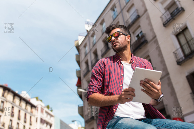 Young handsome man in sunglasses using tablet on urban background.