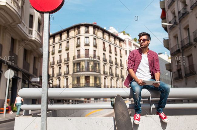 Young trendy man sitting on fence with tablet and long board on urban background.