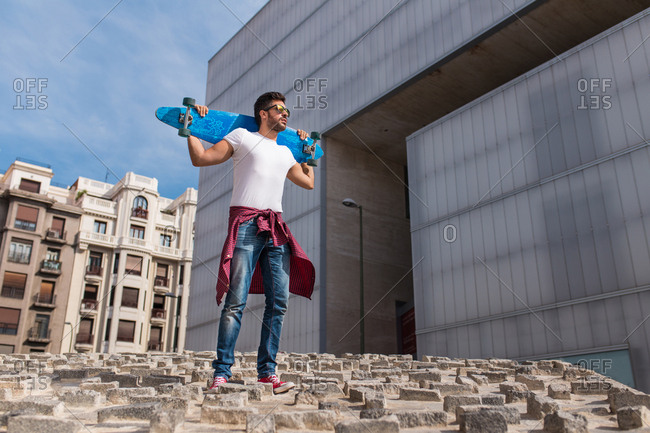 Young trendy man in casual clothing posing with skateboard on urban background.
