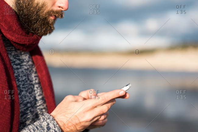 Crop faceless shot of bearded male in warm clothing using phone in nature.