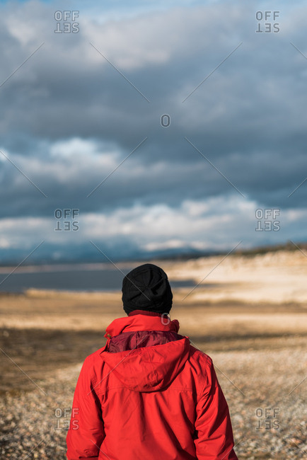Back view of man in warm clothing standing on background of plain with lake in gloomy day.
