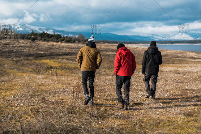 Back view of three people wearing warm clothing and walking on beach in winter time.