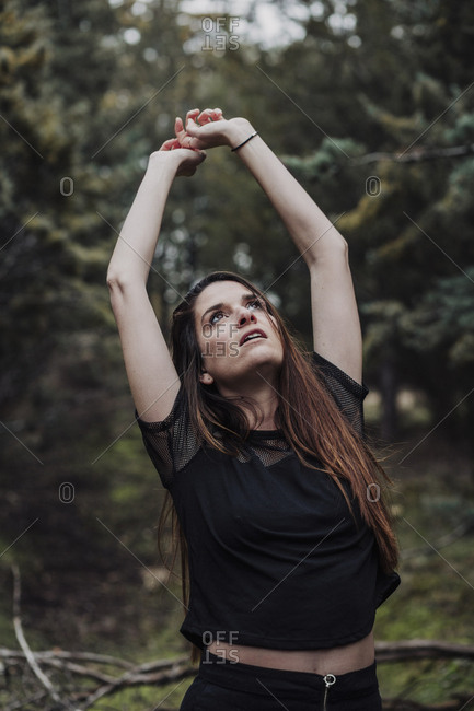 Vertical portrait of a woman posing in the forest and looking up with hands up.