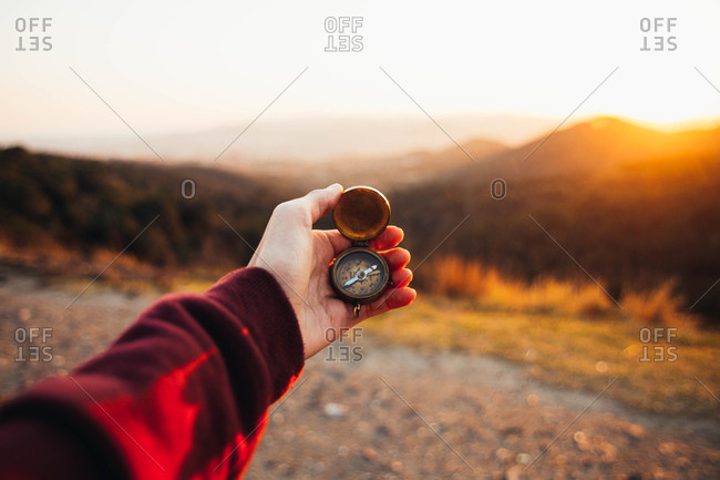 Crop hand of person standing in hills and holding compass. Horizontal outdoors shot.