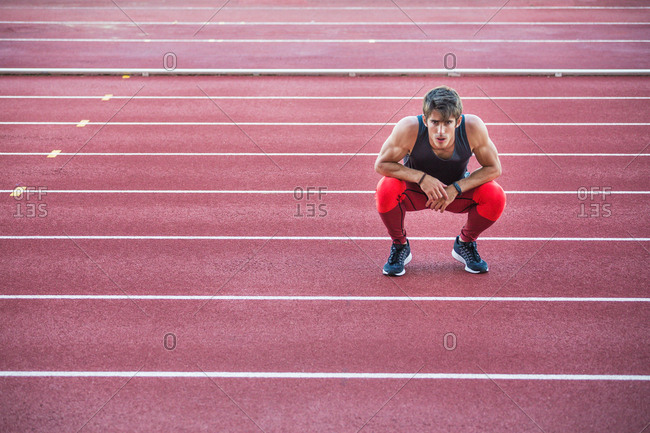 Young muscular man in sportswear squatting on race track.