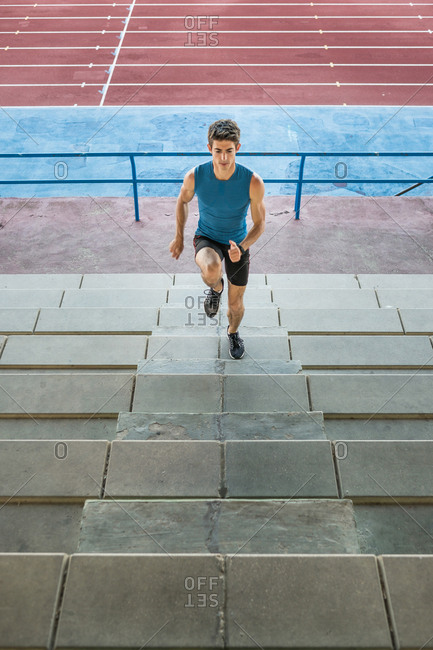 Young muscular man in sportive outfit running up stairs on background of stadium.
