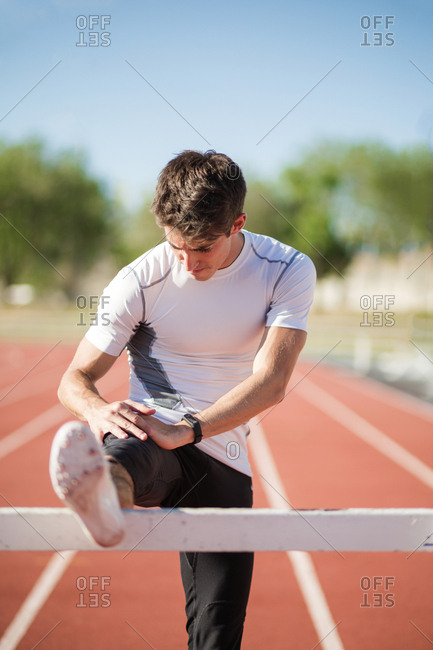 Young sportsman in outfit warming up legs on race track of stadium.