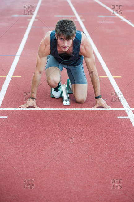 Young concentrated sportsman on crouch start with starting block looking at camera.