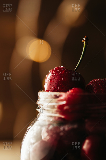 Glass jar with cherry berries on wooden table. Bokeh lights background.