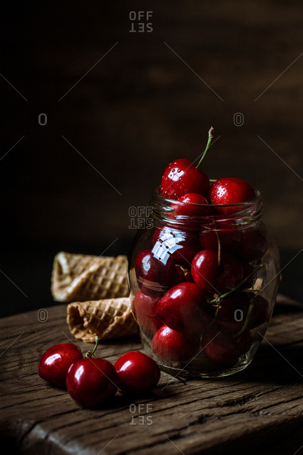 Jar filled with cherry and waffle cones on wooden counter.