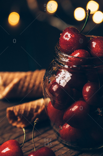 Fresh cherry berries in jar and waffle cones on table. Bokeh lights background.