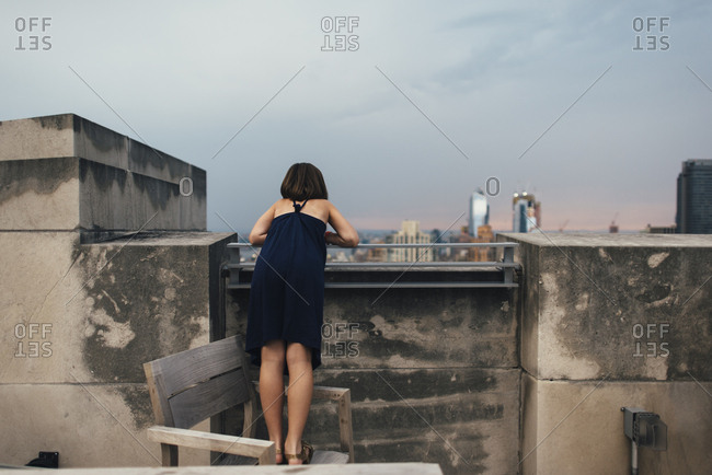 Little girl overlooking New York City from rooftop