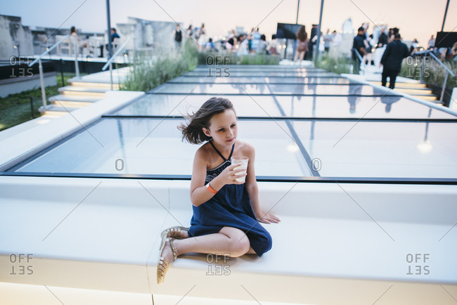 Little girl having drink at a rooftop party