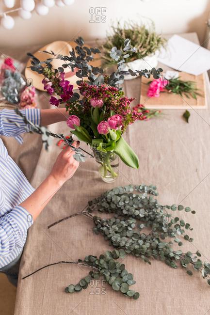Crop woman arranging flowers