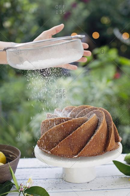 Woman putting powdered sugar on a bundt cake