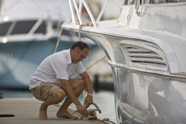 A man tying his boat to a mooring