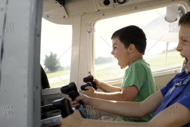 Two young boys pretending to be pilots in the cockpit of a plane