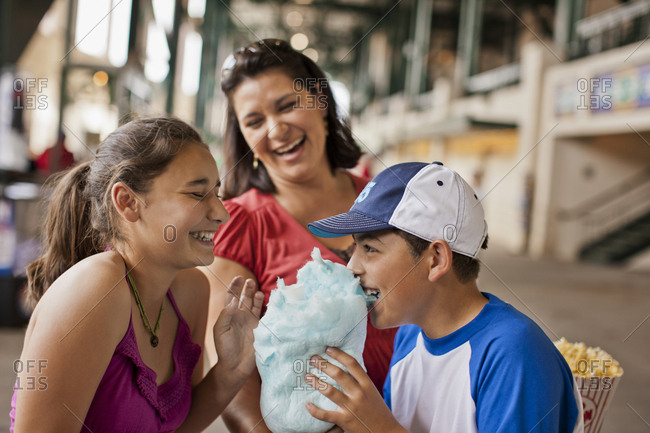 A mother watching as her son and daughter eat cotton candy at a funfair