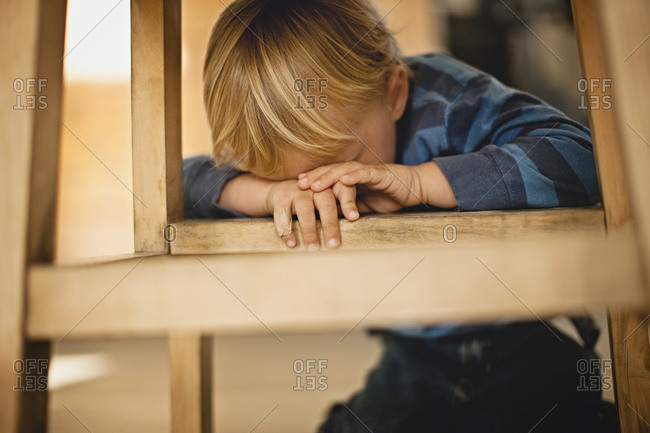 A young boy hiding under a wooden stool