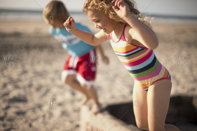 A young boy and girl jumping into the sand at the beach
