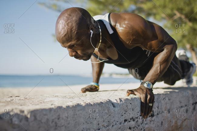 A man exercising on a stone wall near the beach