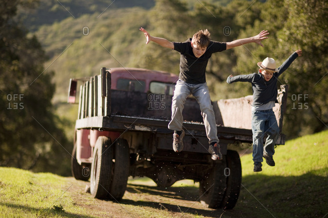 Two young boys jumping from the back of a pickup truck