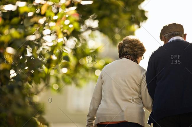 A senior couple walking arm in arm