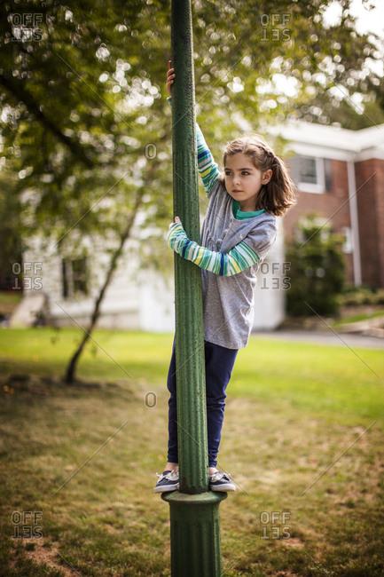 A young girl climbing a streetlight pole in a park
