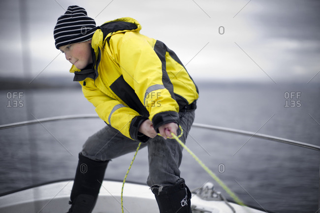 A young boy pulling a rope on a boat