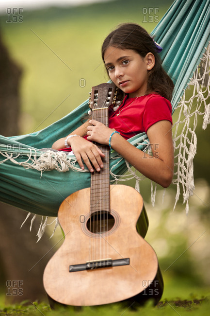 A young girl in a hammock with a guitar