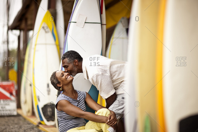 A couple kissing next to a surfboard stand on the beach